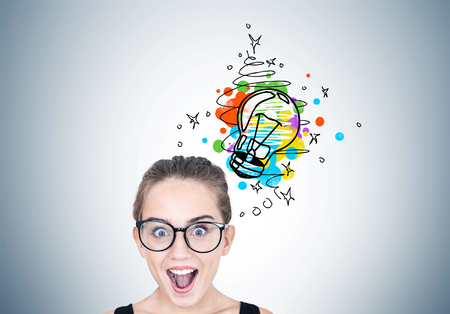 Close up portrait of a young astonished woman wearing round glasses and standing with an open mouth near a gray wall with a small colorful light bulb sketch on it.