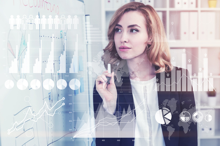 Concentrated and gorgeous businesswoman with red hair is holding a marker and looking at a scheme she drew. Toned image double exposure Elements of this image furnished by NASA