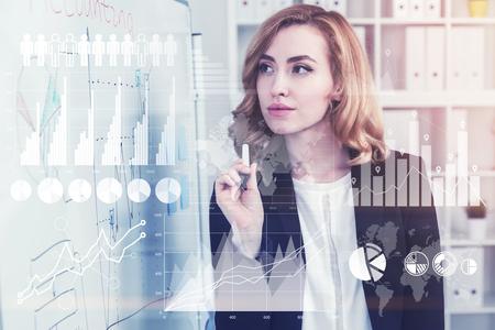 La empresaria concentrada y magnífica con el pelo rojo está sosteniendo un marcador y está mirando un esquema que ella dibujó. Imagen tonificada doble exposición Elementos de esta imagen proporcionada por la NASA