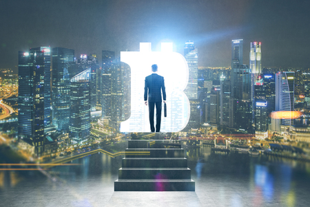 Rear view of a businessman wearing a suit and ascending the stairs in a night cityscape room with a large bitcoin sign opening in the wall. Toned image mock up