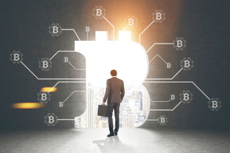 Rear view of a businessman holding a suitcase and looking at a cityscape standing in a dark room with bitcoin network sketch and a large bitcoin sign opening in the wall. Toned image mock up Stock Photo