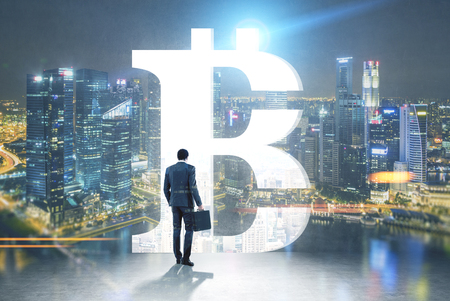 Rear view of a businessman holding a suitcase and looking at a night cityscape standing in a room with a large bitcoin sign opening in the wall. Toned image mock up