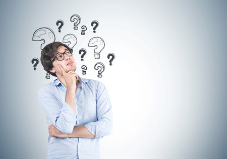 Portrait of a young man wearing a blue shirt, jeans and glasses and thinking. He is standing near a gray wall with many question marks on it. Mock up