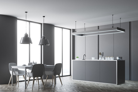 Kitchen interior with a wooden floor and gray countertops. A table with chairs in the foreground. 3d rendering mock up