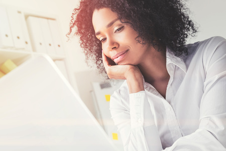 Portrait of a pensive beautiful African American businesswoman looking at her laptop screen. Toned image