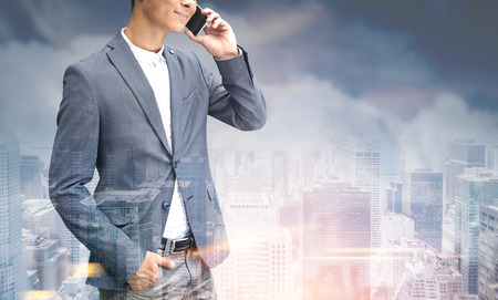 Portrait of a young unrecognizable businessman in a suit talking on the phone and smiling. He is standing against a gray city background. Toned image mock up Stock Photo