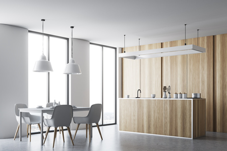 Kitchen interior with a concrete floor and wooden countertops. A table with chairs in the foreground. 3d rendering mock up