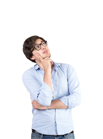 Isolated portrait of a young man wearing a blue shirt, jeans and glasses and thinking. Concept of planning Stock Photo