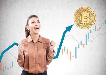茶色のブラウスを着て、ビットコインとグラフが付いた具体的な背景に立って喜びで叫ぶ若いビジネスウーマンの肖像画 写真素材