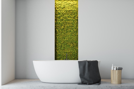 White bathroom interior with a concrete floor, a white bathtub, a sink, several closets and a narrow window with shrubbery behind it. Close up. 3d rendering mock up Reklamní fotografie