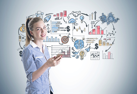 Portrait of a smiling young businesswoman wearing a blue shirt and holding a smartphone. A gray wall background with a business strategy sketch