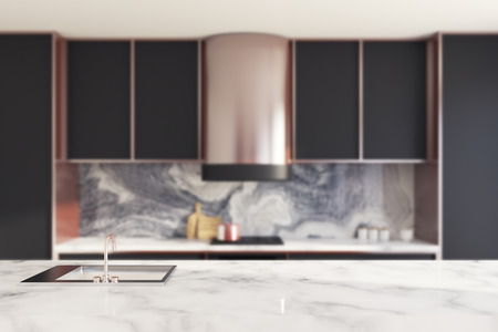 Close up of black countertops and cupboards with built in appliances. A white marble table in the foreground. Blurred. 3d rendering mock up Imagens
