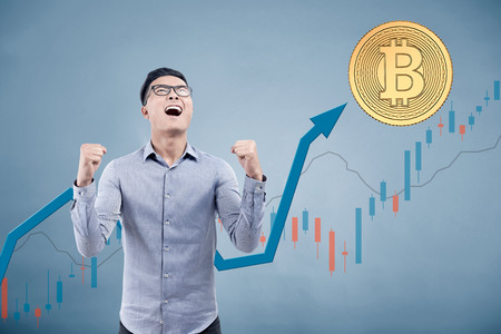 Portrait of a young Asian businessman wearing glasses and yelling with joy standing against a gray background with a bitcoin and graphs on it