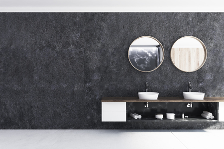 Black bathroom interior with a concrete floor, a double sink and two round mirrors. 3d rendering mock up Фото со стока