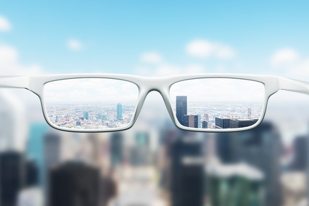 Day cityscape with skyscrapers and a blue sky as seen through a pair of glasses. Blurred image. Stockfoto