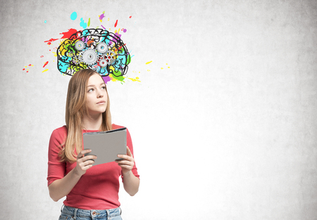 Young blonde woman wearing a pink sweater and jeans and holding a folder is looking sideways. A concrete wall with a brain with gears on it. Mock up