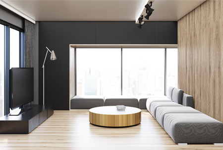 Black living room interior with a wooden wall and floor, a gray sofa, a TV set and a round coffee table. 3d rendering Stock Photo