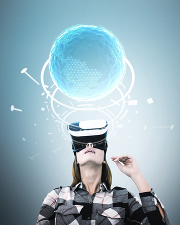 Portrait of a young woman in a checkered shirt wearing VR glasses and looking upwards. A gray background. An Earth hologram.