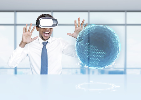 Happy African American man wearing VR glasses and a shirt with a tie interacting with an Earth hologram. Toned image double exposure Elements of this image furnished by NASA Stock Photo
