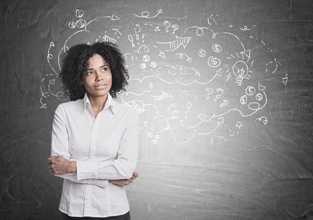 Portrait of a thoughtful African American businesswoman wearing a white blouse and standing with crossed arms. A blackboard with an arrow sketch