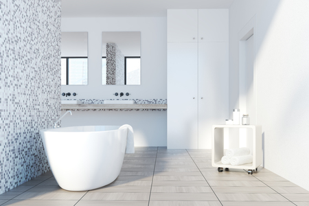 Gray tile and white bathroom interior with a white tub and a trolley with rolled towels. 3d rendering mock up