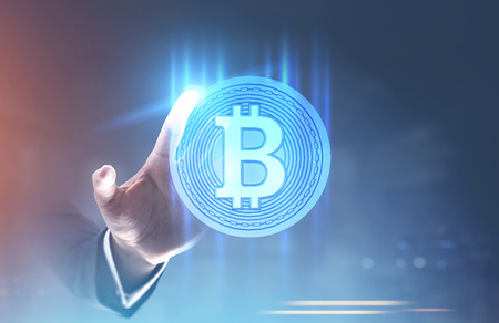 Hand of a businessman in a suit reaching for a shining bitcoin sign inside of a round badge. A blurred abstract background. Toned image double exposure mock up