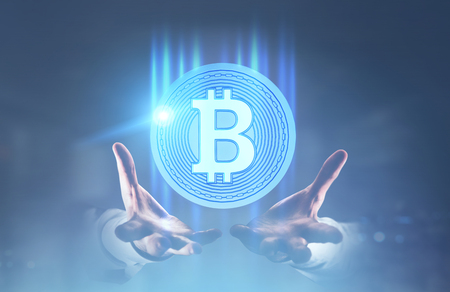 Unrecognizable businessman s hands holding a round bitcoin hologram. A blurred blue background. Toned image double exposure mock up.