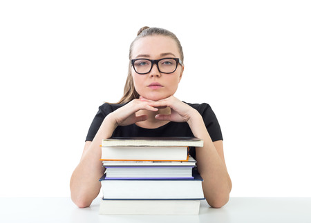 Isolated portrait of a serious young woman in glasses looking forward and sitting with her chin on a stack of books. Concept of education. Standard-Bild