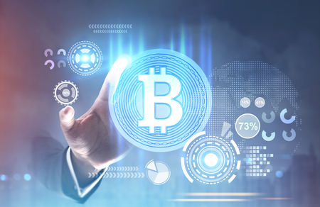 Hand of a businessman in a suit reaching for a shining bitcoin sign inside of a round badge. HUD. A futuristic background, a blurred abstract interface. Toned image double exposure mock up