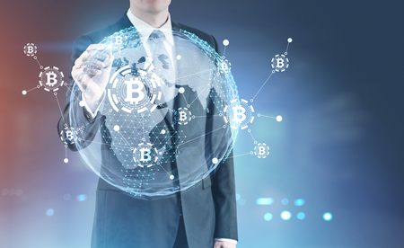 Unrecognizable businessman with a glowing marker standing against a blurred background with a bitcoin hologram in front of him. Toned image double exposure Elements of this image furnished by NASA