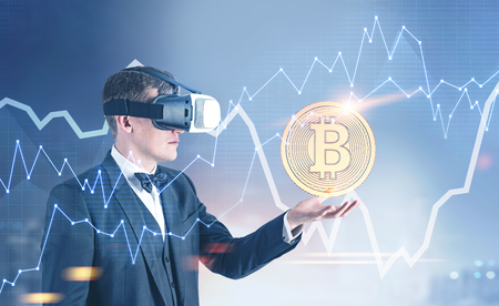 Side view of a handsome fair hair businessman wearing VR glasses, a bow tie and a suit. He is holding a bitcoin. Graphs and a cityscape background. Toned image double exposure Stock Photo