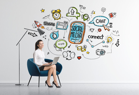 Charming young businesswoman sitting in an armchair in a room with concrete walls and a social media sketch Stock Photo