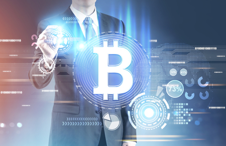 Close up of an unrecognizable businessman with a glowing marker standing against a blurred background with a bitcoin hologram in front of him. Toned image double exposure