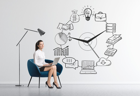Charming young businesswoman sitting in an armchair in a room with concrete walls and a time management sketch