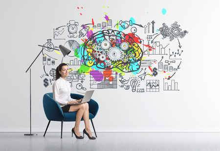 Charming young businesswoman sitting in an armchair in a room with concrete walls and business strategy sketch and a brain with cogs.