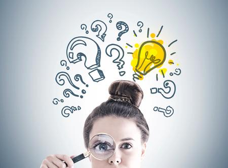 A cabeça da mulher de negócios com uma lupa perto de seu olho. Uma parede cinza com um esboço de lâmpada e pontos de interrogação sobre ele.