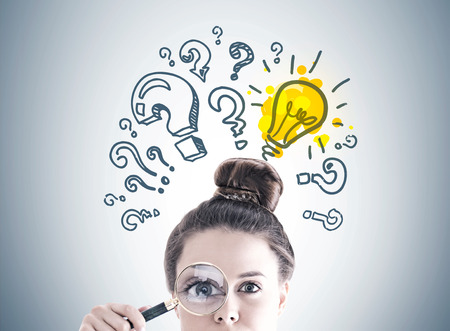 Businesswoman s head with a magnifying glass near her eye. A gray wall with a light bulb sketch and question marks on it. Stockfoto