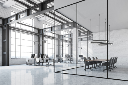 Loft office interior with a white table, white brick walls, loft windows and rows of computer tables with black screens. A meeting room to the right. 3d rendering mock up