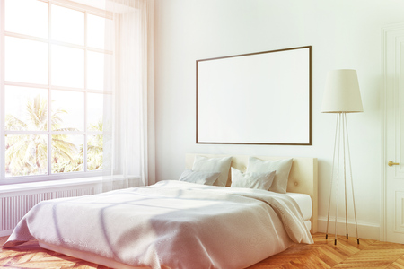 White bedroom corner with a white bed, a lamp and a framed horizontal poster hanging above the bed. 3d rendering mock up toned image Banque d'images - 94793432