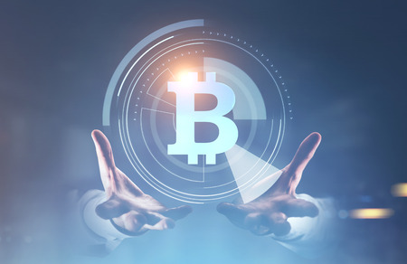 Unrecognizable businessman hand holding a bitcoin HUD, infographics and immersive interface. A blurred background. Toned image double exposure mock up
