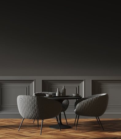 Black round table standing in a cafe with gray chairs near it and a dark gray wall in the background. 3d rendering mock up Stock Photo