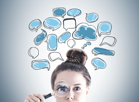 Businesswoman s head with a magnifying glass near her eye. A gray wall with a blue speech bubbles sketch on it.