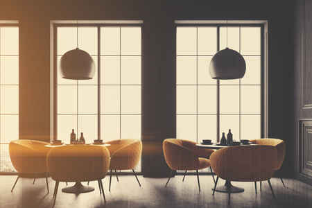 Interior of a black cafe corner with a concrete floor, round black tables and yellow chairs. 3d rendering mock up toned image double exposure Stock Photo