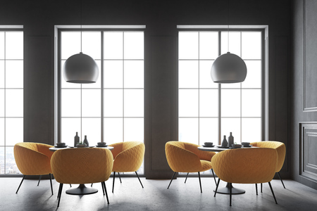 Interior of a black cafe corner with a concrete floor, round black tables and yellow chairs. 3d rendering mock up Stock Photo