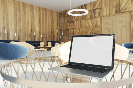 White screen laptop standing on a round coworking table. There are tables with armchairs in the background. 3d rendering mock up