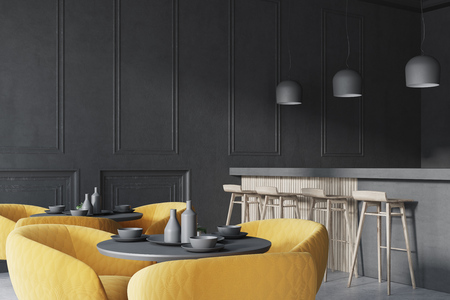 Black cafe corner with a concrete floor, round black tables and yellow chairs. A bar with stools. 3d rendering mock up Stock Photo