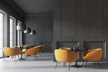 Black cafe interior with a concrete floor, round black tables and yellow chairs. A blank wall fragment. 3d rendering mock up Stock Photo