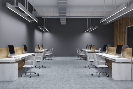Wooden and gray wall open space office interior with a concrete floor and white computer tables. 3d rendering mock up