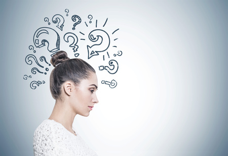 Side view of a calm and beautiful young european woman with a bun wearing a white sweater. A gray wall with question marks. Mock up Foto de archivo