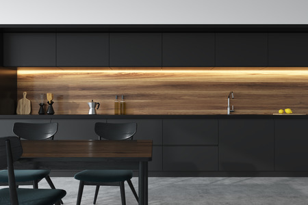 Front view of a panoramic black and wooden kitchen interior with dark gray countertops and a table with chairs. 3d rendering mock up Stock Photo